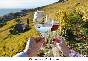 Two hands holding wineglases against vineyards in Lavaux...