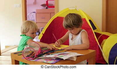 siblings sketching with pencils in home