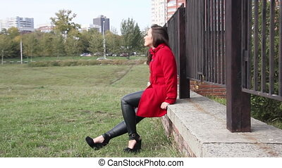 Young beautiful girl sits on a brick parapet and goes around...