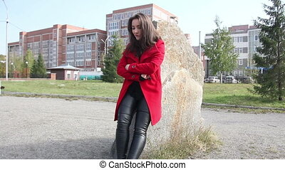 Beautiful girl in a red coat waiting leaning against a large rock