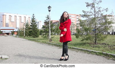 Beautiful girl in the red coat is waiting, standing in the...