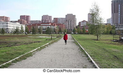 Beautiful girl in a red coat walking on path in park