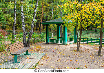 Bench and pavilion in autumn park - Landscape with bench and...