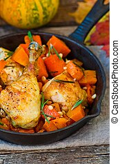 the baked chicken with pumpkin in a pig-iron frying pan on...