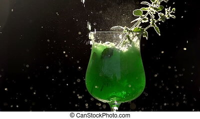 Green Soda Being Poured into a Glas - Emerald-green drink is...