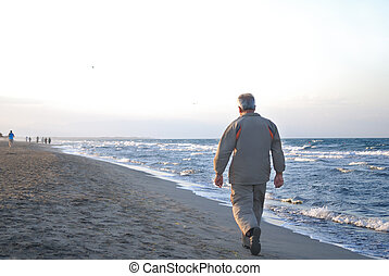 lonely older man walking on beach
