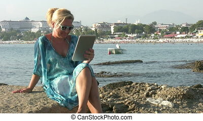 Woman using digital tablet on the beach
