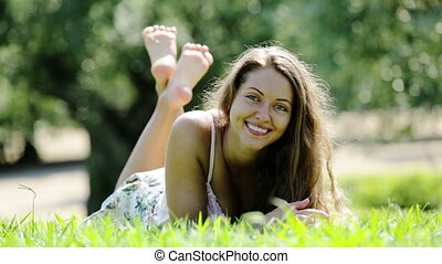 Happy girl laying outdoor in grass meadow