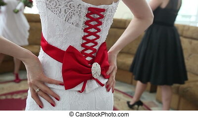 bride corset tie on the back of a red ribbon and bow