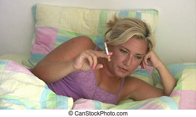 Sad woman lying on a bed and smoking  cigarette