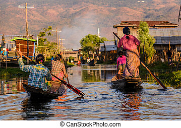 Burmese women rowing on wooden boats, Inle Lake, Myanmar...