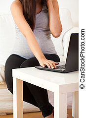 Pregnant woman working at home - View of pregnant woman...