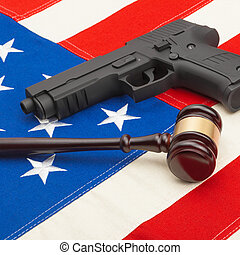 Gun and wooden judge gavel over USA flag - studio shoot - 1...