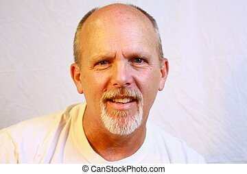 Bald man with white goatee and white shirt. - Bald man with...