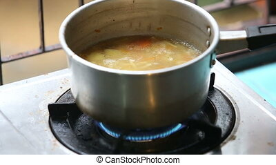 stirred ladle chicken soup in saucepan on gas stove -...