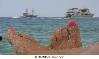 Summer holiday scenics at the beach - Female foot on sandy...