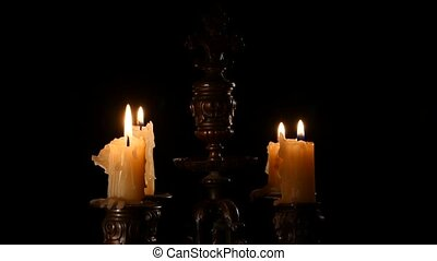 Candle in vintage candlestick on black background
