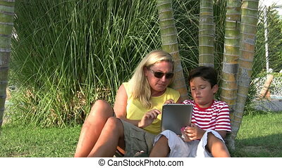Mother and son using digital tablet in the park