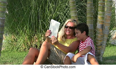 Mother and son sitting in the park and taking selfie