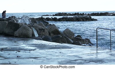 Sea wave impinges on an old stony rocky pier