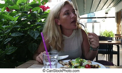 Woman eating salad and meat in restaurant