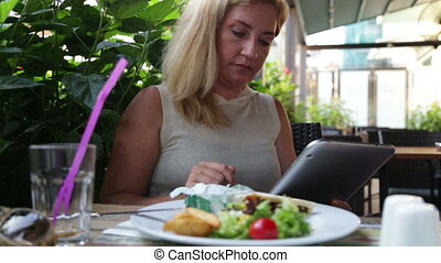 Woman with digital tablet in cafe - Woman in cafe using...