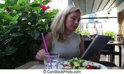Woman in cafe using touchpad and eating