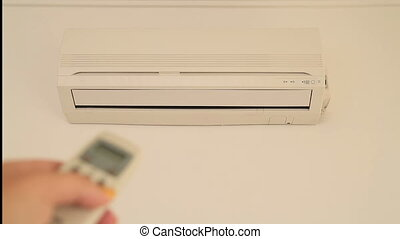 Hand controlling an air conditioner