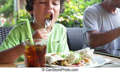 child eating at the cafe - Hungry child eating at the...