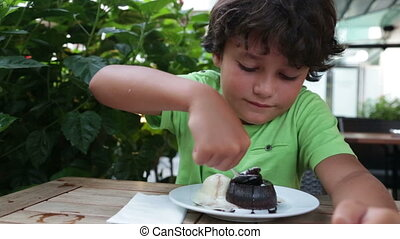 Child eating chocolate souffle at the restaurant