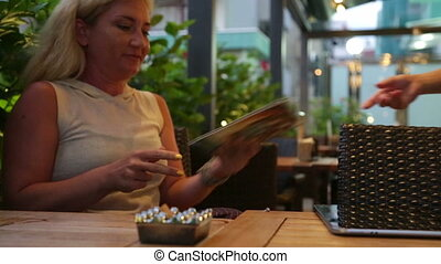 Woman paying for cafe - Woman sitting at cafe table in cafe,...