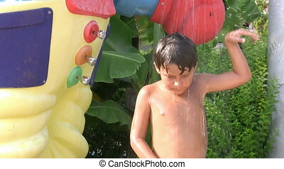 Child taking a cold shower and dancing in a waterpark