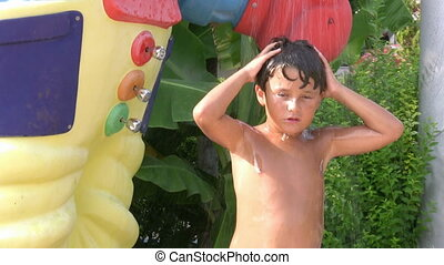 child taking a cold shower in a waterpark