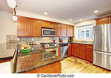 Maple kitchen cabinets with steel appliances and granite tops