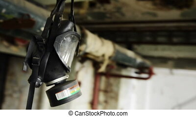 Black gas mask hanging from the ceiling in a bulding