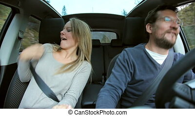 Couple dancing in car happy - Blond woman and man dancing...