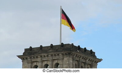 waving german flag on top of Bundestag