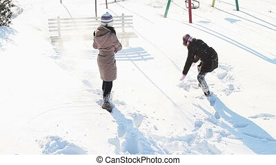 Girls having fun in snow in a citypark