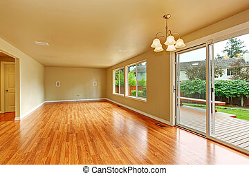 Empty living room with exit to backayrd deck