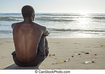 Beach life - Back view of lean young shirtless African...