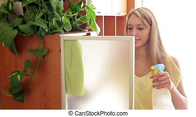 girl in yellow cleaning glass door - Blonde girl in yellow...