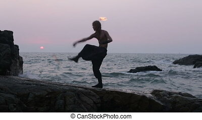 man turns fire poi standing on a cliff near the ocean at...