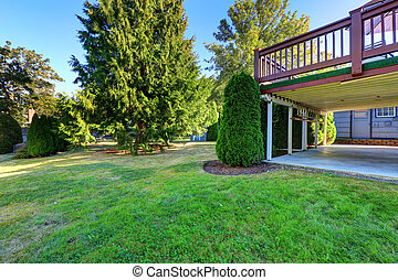 House with walkout deck and backyard landscape