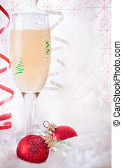 Glass with Champagne and Christmas baubles on the Snowy...