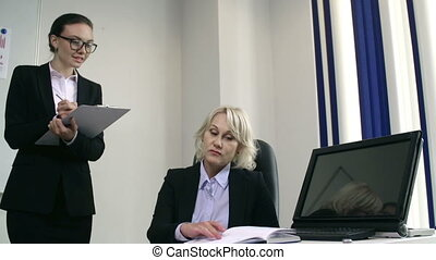 Women in Business - Bossy lady seated at the desk dictating...