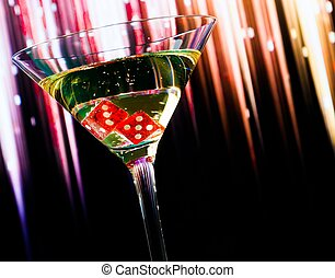 red dice in the cocktail glass on colorful gradient with...