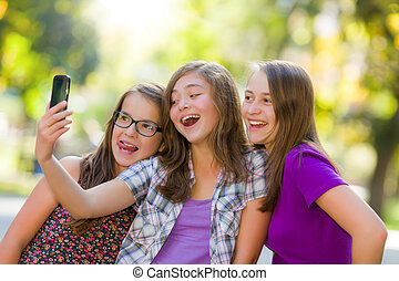 Happy teen girls taking selfie in park with mobile phone