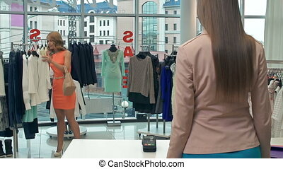 Buying a Dress - Sales assistant standing with her back to...