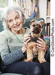 Senior Woman Holding Pet Dog Indoors