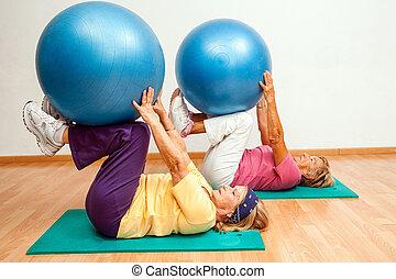 Senior women exercising with gym balls. - Two Senior women...